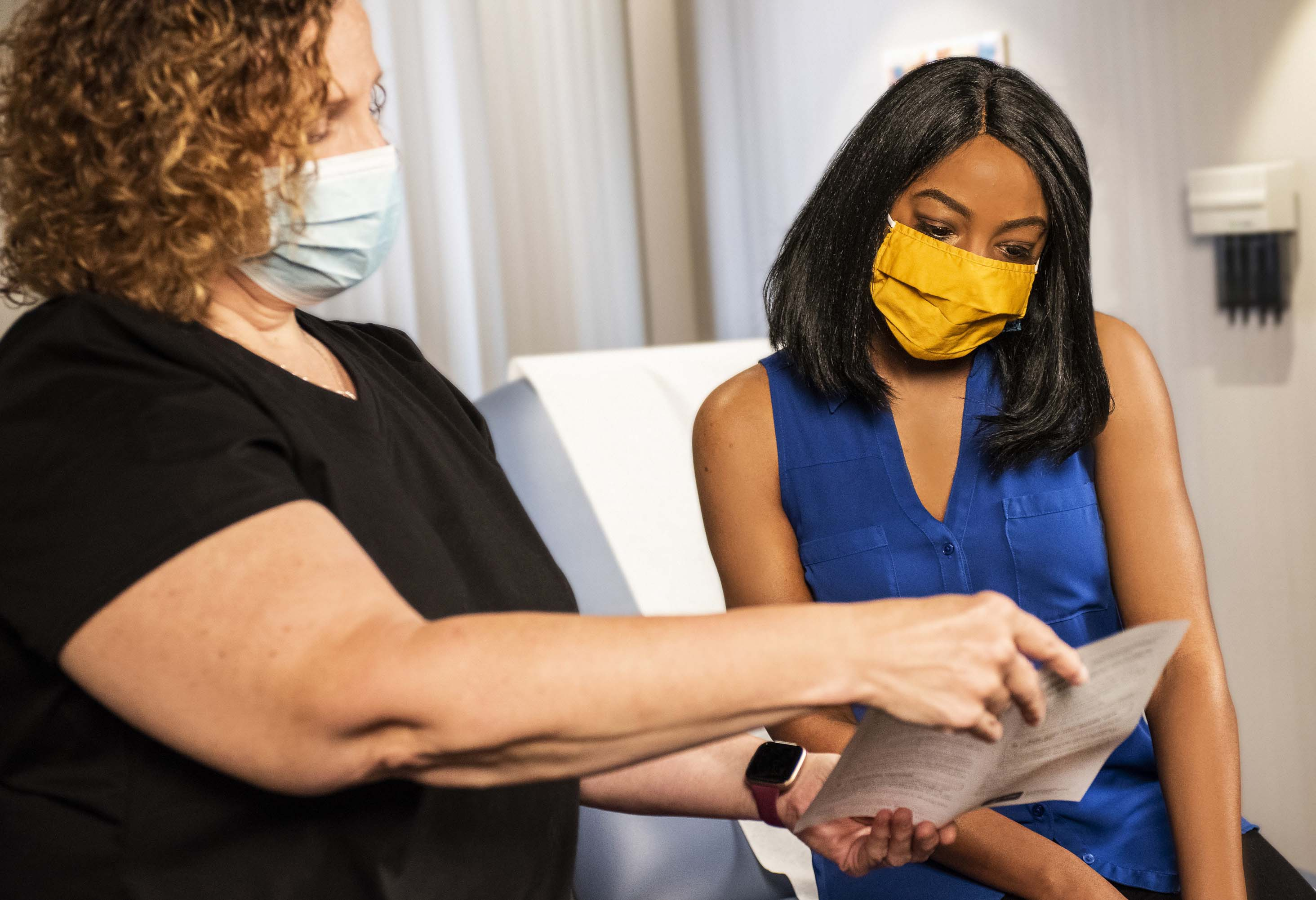 A medical professional shows a patient some printed-out information in a consulting room.