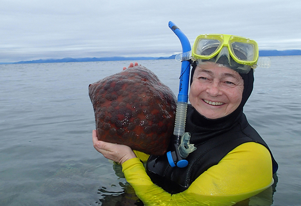 A person (Maria Byrne) standing in calm water in snorkelling gear, smiling and holding a sea star