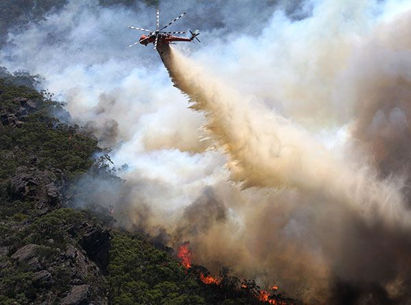 A helicopter dropping water on a bushfire.