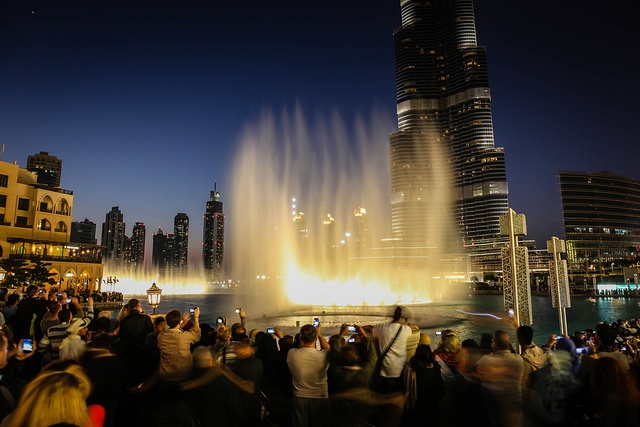A group of people watching a fountain beneath skyscrapers in Dubai