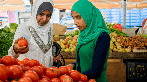 Two women examining vegetables in a market.