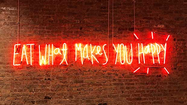 A photo of a neon sign on a brick wall that reads eat what makes you happy.