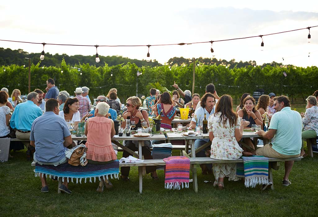 Some long dining tables and chairs, outdoors on a lawn, with many people enjoying a meal together.
