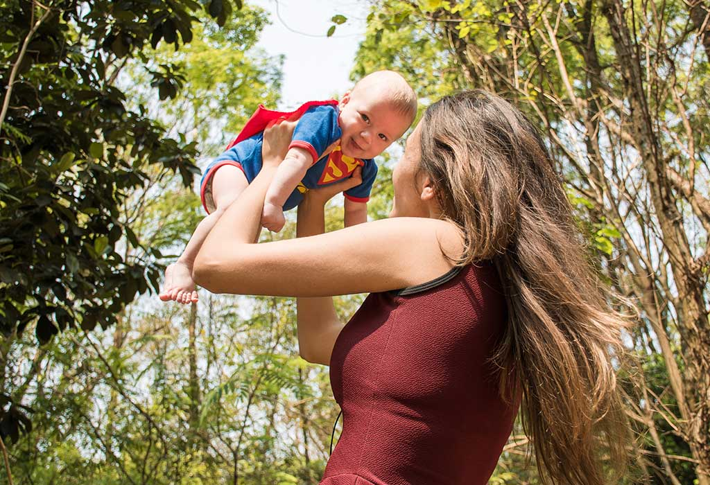 A mother holding up her baby, who wears a Superman costume