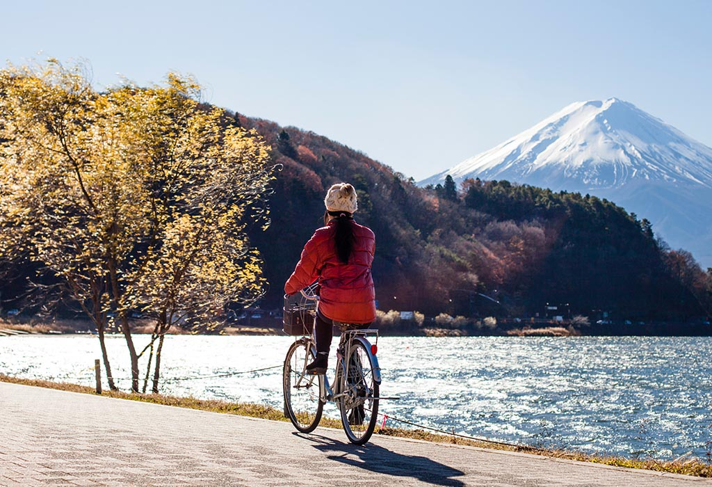 Someone riding a bike past a lake, with mountains in the background