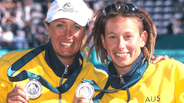 Two athletes holding medals.