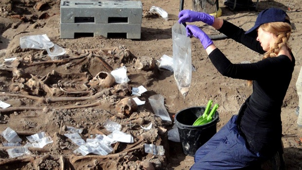 An archaeologist sampling remains from a mass grave