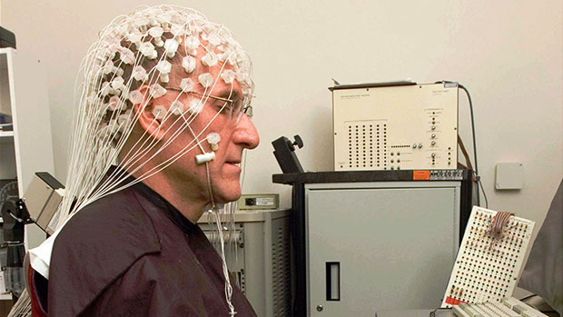 Picture of a person wearing a research EEG headset with many electrodes