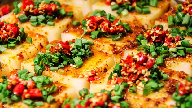 Light brown slices of tofu topped with chilli and spring onion