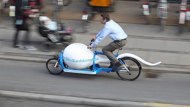 A man riding a sperm-shaped bike
