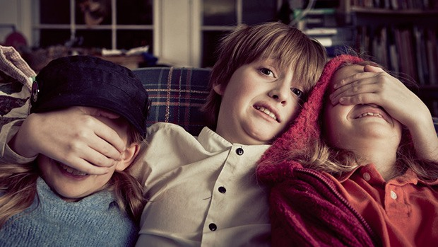 Three kids watching a scary movie