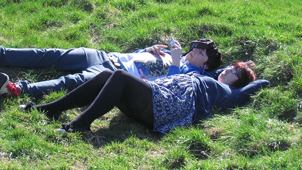 Two teenagers lying in a grassy field