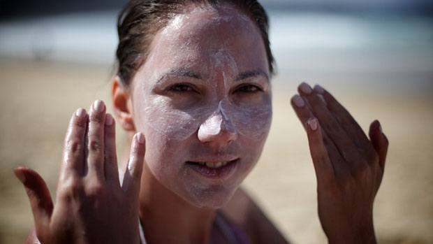 Woman putting sunscreen on her face.
