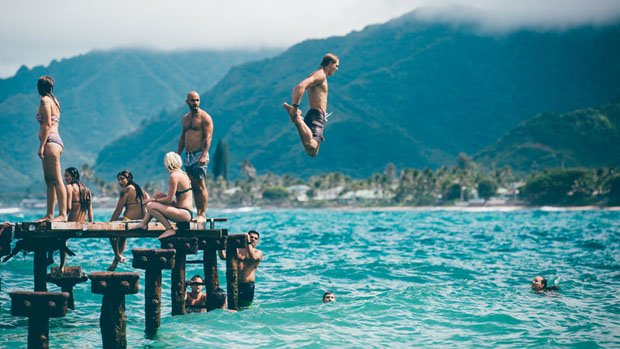 Man jumping off a pier into water.
