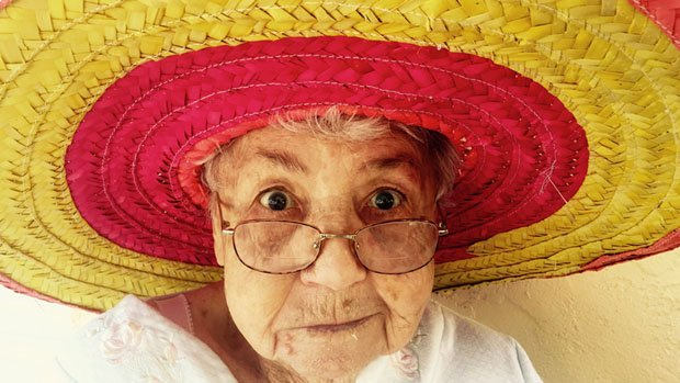 Old woman wearing a colourful sombrero.
