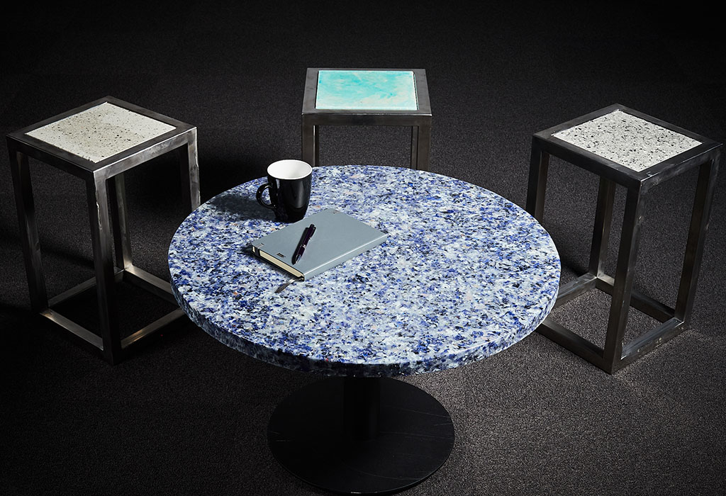 A round coffee table and three stools with textured appearance
