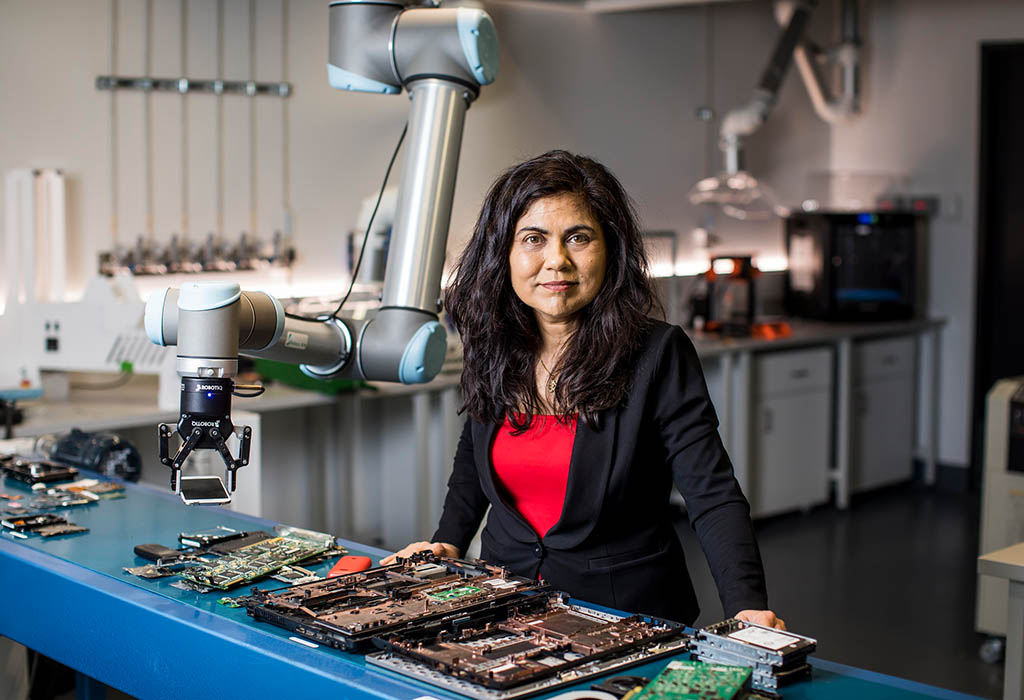 Prof Veena Sahajwalla standing in front of a table with electronic components on it