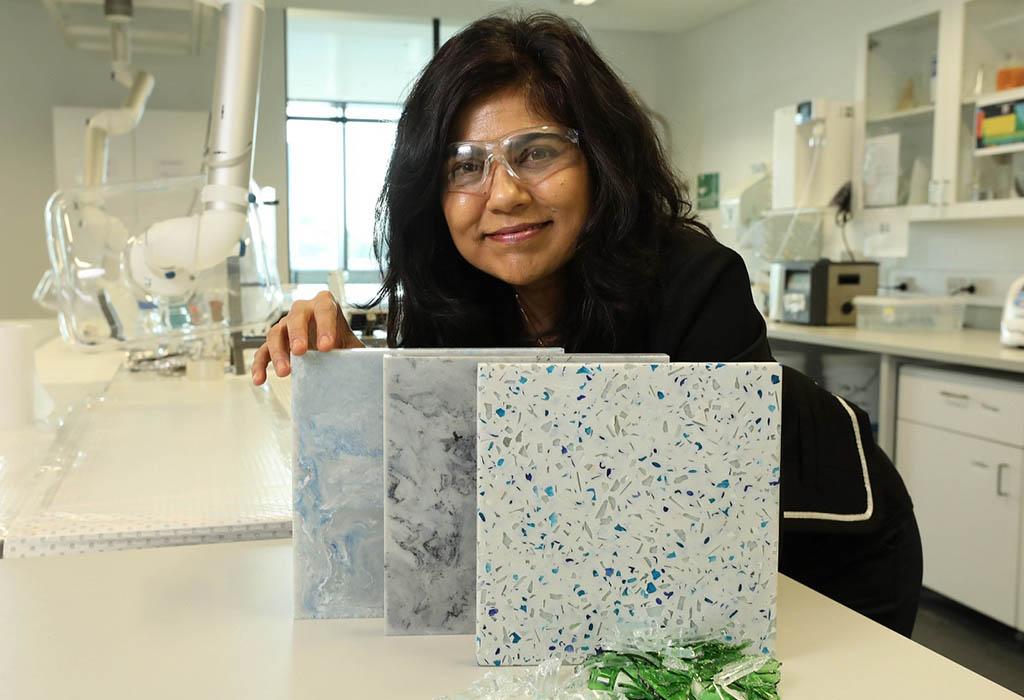 Prof Veena Sahajwalla holding some ceramic tiles with textured appearance