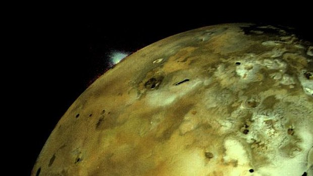 A photo of Io with a huge volcanic eruption visible from space.