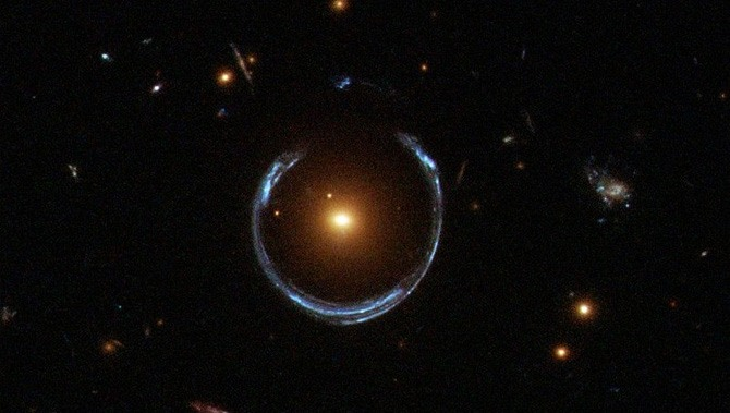 Light from one faraway galaxy is distorted into a ring around a closer galaxy.