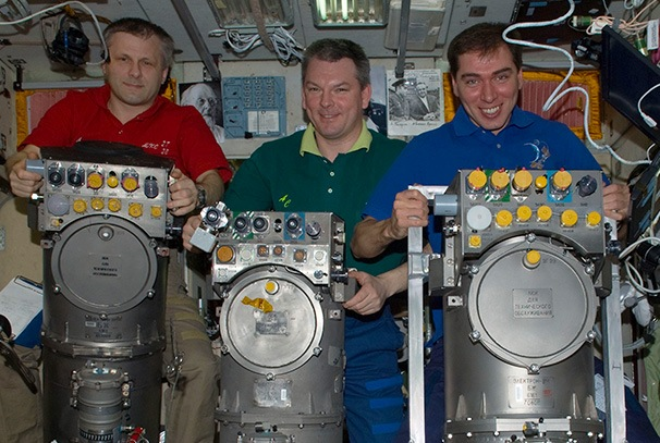 Russian cosmonauts with oxygen generator systems on the International Space Station.