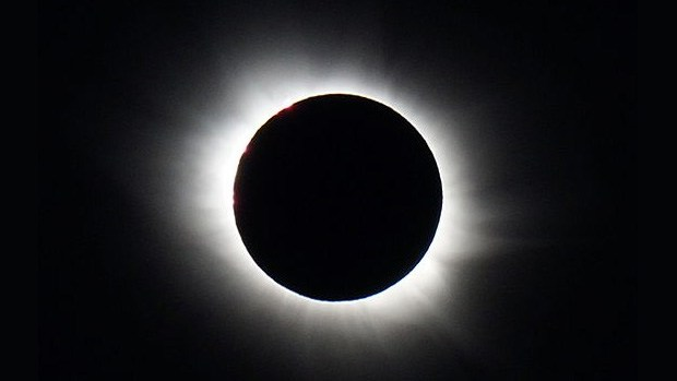 The sun during a total solar eclipse, with the outer corona visible beyond the shadow of the moon.