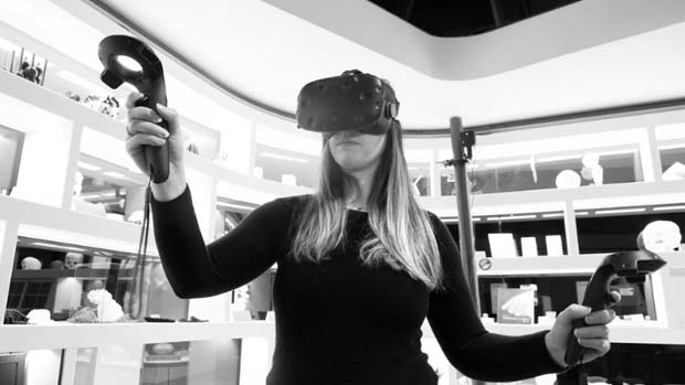 Woman wearing VR headset and holding controllers.