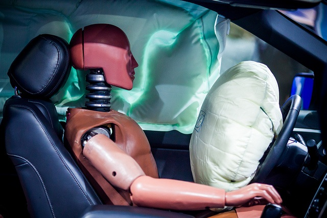 A crash test dummy in front of an inflated airbag.