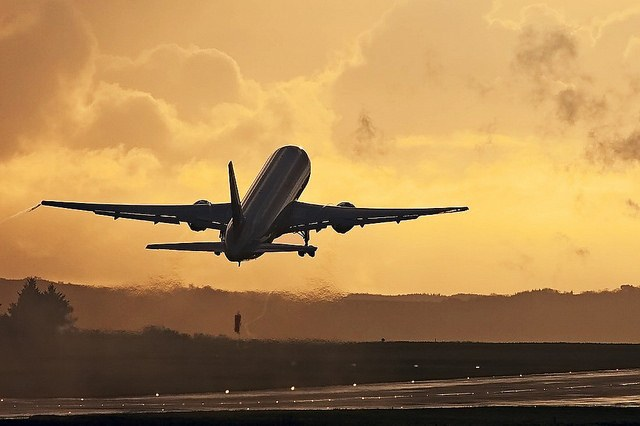 A Boeing 767 plane taking off at sunset.