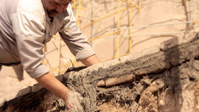 A man reconstructing an ancient mud brick citadel in Iran after it was damaged in an earthquake.