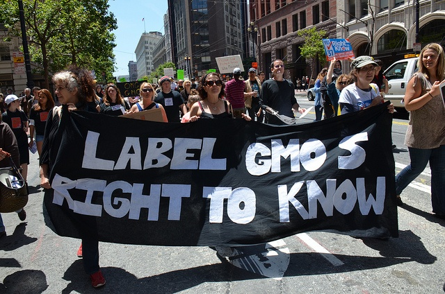 Protesters hold signs to support the labelling of genetically modified foods.