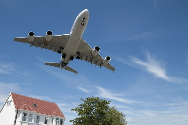 Jet aircraft landing approach over suburban housing
