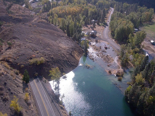 Aerial view of landslide burying a road and a damming a river