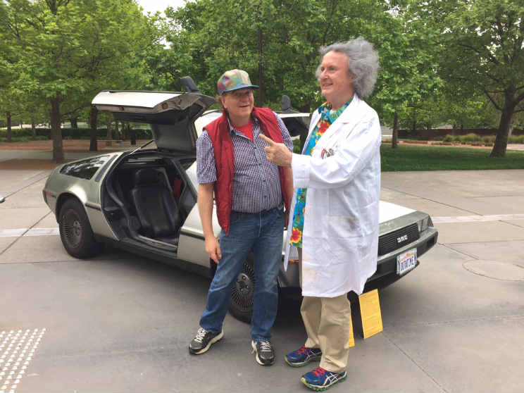 Brian Schmidt and Les Field dressed as Marty and Doc standing in front of a DeLorean