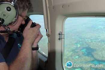 Professor Terry Hughes taking photos of a reef from a plane