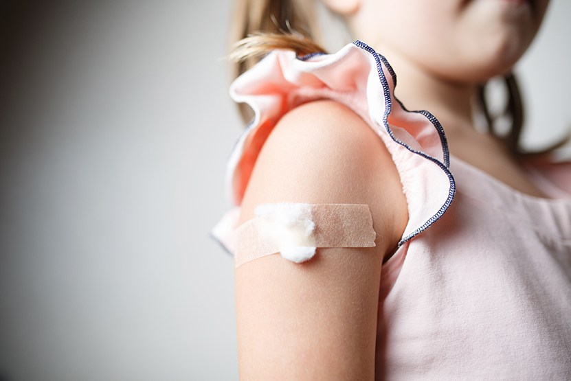 Upper arm of young girl with bandaid on it