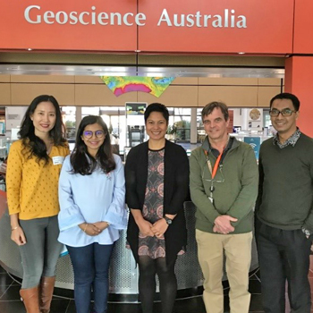 People standing in front of a Geoscience Australia sign