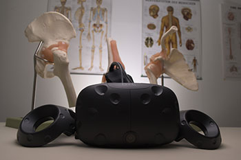 A VR headset with anatomy posters and bone samples in background